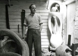 Henry Moore in his studio Perry Green c. 1953-54, with working model plasters for Upright Internal External Form (r.) and the elmwood carving in progress (l.) © The Henry Moore Foundation